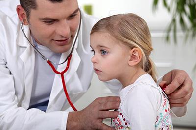 врач прослушивает маленькую девочку